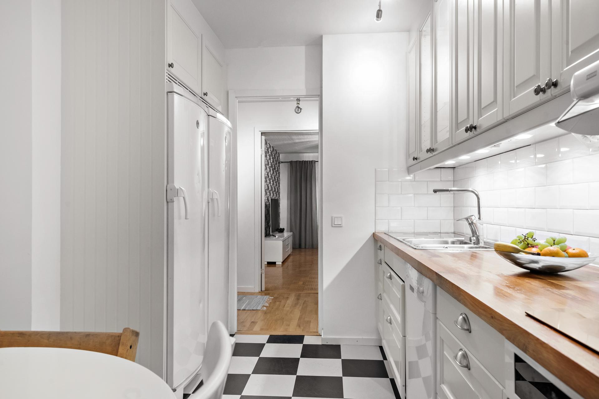 Det moderna köket med lantliga toner och en super-modern linoliummatta i schakrutigt mönster
